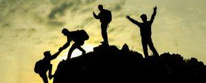 teamwork of 4 climbers reaching mountain top at dusk