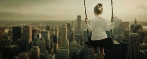 young girl on swing over cityscape